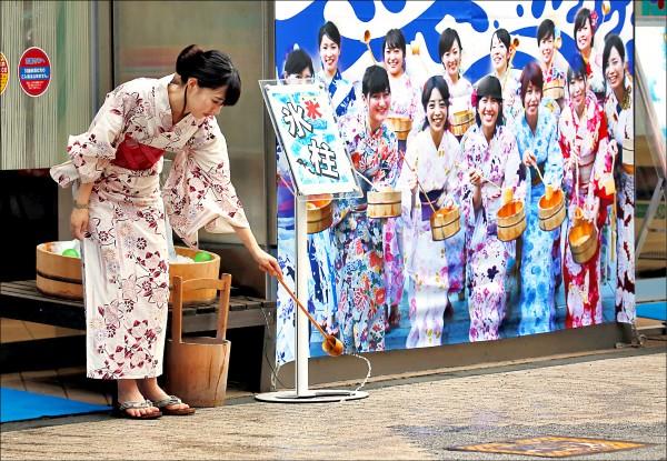 身穿浴衣年輕女子在東京一家柏青哥店外,將木桶內的水,以木勺子朝柏油路潑灑,此舉名為「打ち水(Uchimizu,灑水之意)」,旨在藉由水分蒸發,讓四周降溫或減少空氣中揚起的灰塵,乃日本夏季常見傳統之一。(路透)
