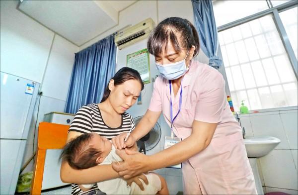中國廣西壯族自治區融安縣一名母親,二十三日帶著孩子到醫院接種疫苗。(歐新社)