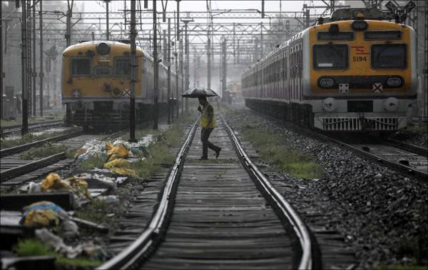 印度經常發生人為造成的列車誤點或事故。圖為一名警察本月初穿越孟買的火車鐵軌,兩列火車因人行天橋崩塌而停駛。(歐新社檔案照)