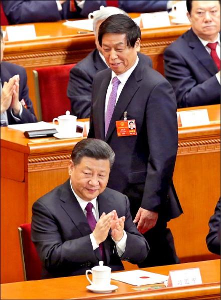 習近平(前)和栗戰書(中)三月在北京人民大會堂出席全國人民代表大會。(路透檔案照)