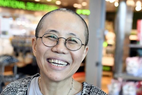 劉霞掙脫中國展現的笑容,讓全球動容。圖為劉霞在芬蘭轉機時,露出的真摰笑臉。(美聯)