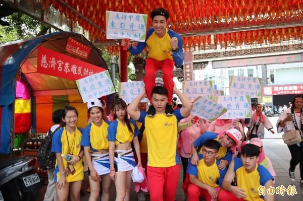 10多位文化大學啦啦隊學生利用參加豐原城隍廟遶境活動,特別舉牌為台中加油。(記者歐素美攝)