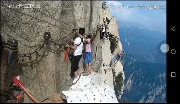 24日下午,一名遊客突然解開身上的安全索,從2000多公尺山壁上的華山「長空棧道」縱身一跳。(圖擷取自微博影片)