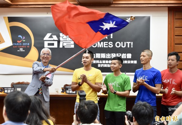 台灣同志運動發展協會23日於立法院舉辦「2018巴黎同志運動會-台灣隊出發」記者會。代表隊榮譽團長祁家威(左一)揮舞國旗,為選手加油。(資料照)