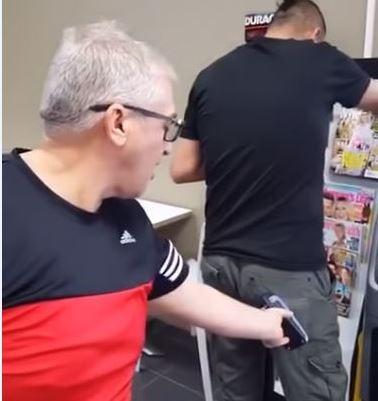 白髮男子拿著行動刷卡機放在黑衣男子屁股後方,企圖「隔空盜刷」信用卡。(圖擷取自影片)