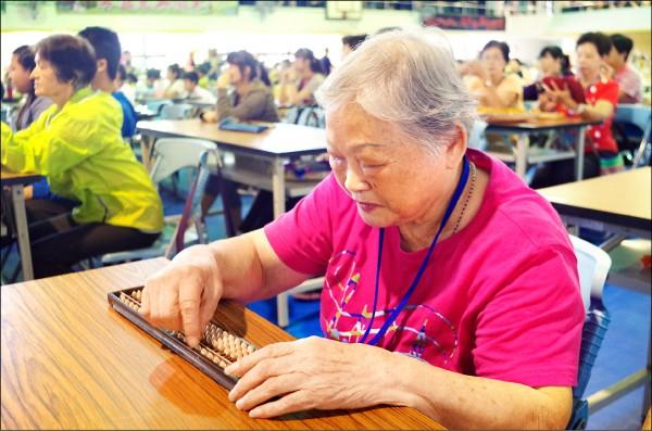 第十四屆洲際珠算比賽在嘉義市舉辦,最高齡的93歲阿嬤蔡黃足治,打起珠算盤手腳靈活。(記者王善嬿攝)