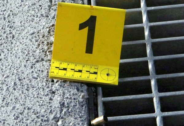 南投縣竹山鎮一家超商大門前發生一起槍擊案,警方標記查扣彈殼情形。(記者謝介裕翻攝)