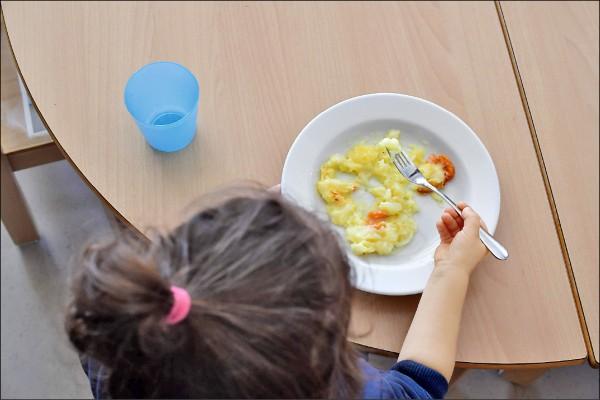 德國柏林葛羅培斯(Gropiusstadt)住宅區內,一名女孩正在幼兒園兼家庭中心吃午餐。(法新社檔案照)