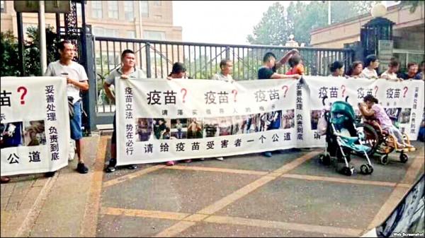 二十多名家長上月三十日帶著孩子聚集在北京的國家衛生健康委員會外,高舉布條要求當局妥善處理問題疫苗造成的傷害。(取自網路)