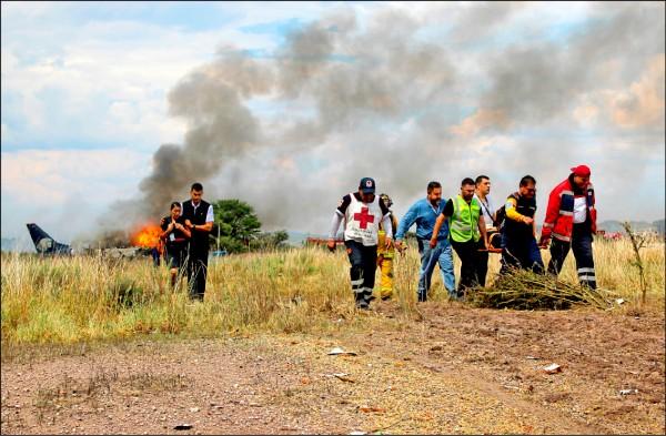 墨西哥國際航空公司一架國內線航班客機,起飛時疑似遭遇強陣風而墜落於跑道盡頭的草叢,飛機墜地後起火燃燒,所幸機上103人全數即時脫困。圖為搜救人員扶著傷者離開現場。(美聯社)