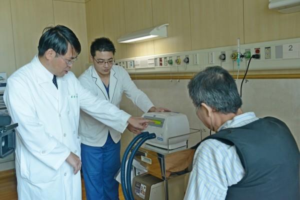 藍冑進(左)教導患者使用拍痰背心。(台北慈濟醫院提供)