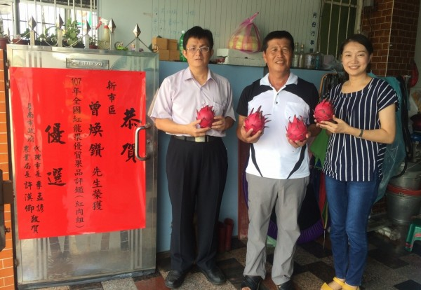 曾煥鑽蟬聯全國紅龍果優質果品評鑑的優選(中),台南市農業局主秘吳威達(左)貼紅紙祝賀。(記者楊金城翻攝)
