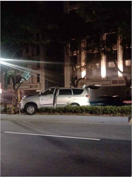 照片中一台銀色休旅車撞上了位於分隔島上的測速照相機,讓照相機的支撐桿直接「腰折」。(圖擷取自爆廢公社)