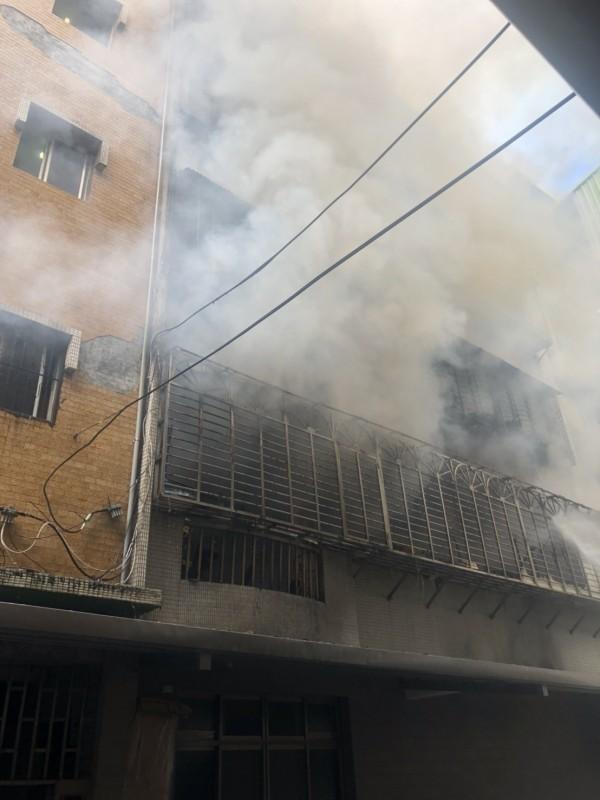 新北市八里區一處民宅,今天上午約8時發生火警,華峰三街52號5樓建築物2樓冒出火煙。(民眾提供)
