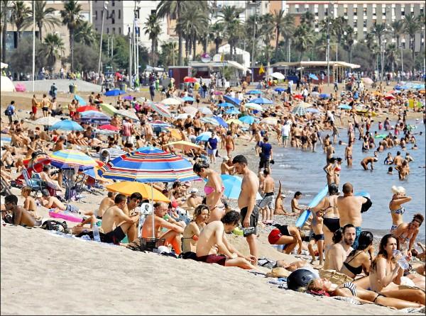 圖為西國巴塞隆納的海灘,4日被渴望消暑的民眾塞爆。(歐新社)