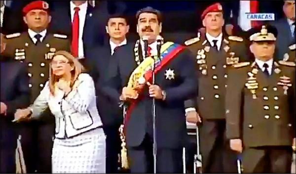 當時站在閱兵台上的委國總統馬杜羅和夫人弗洛雷斯看似受到驚嚇,神色慌張。(法新社)