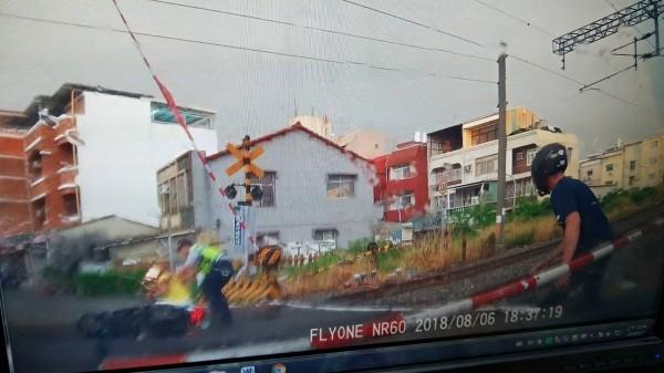 警、民闖進放下欄杆的鐵路平交道,搶救倒地婦人。(記者王俊忠翻攝)