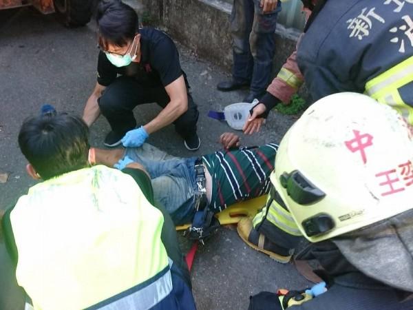 警消人員救出受困工人,準備將他送醫急救。(記者曾健銘翻攝)