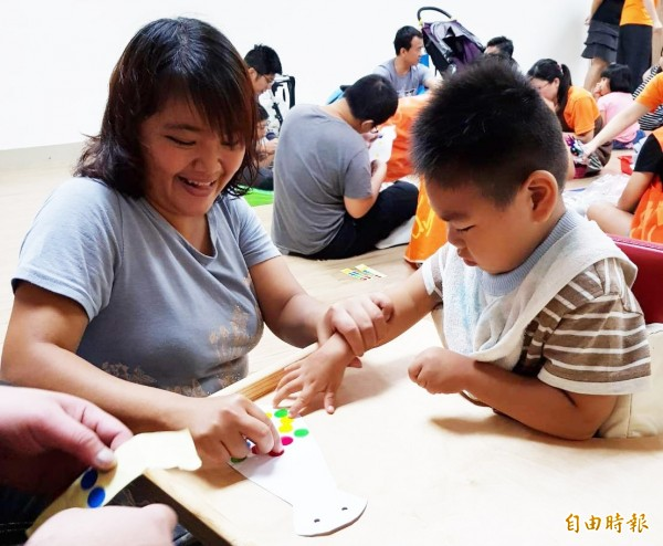 慢飛天使「小智」與媽媽一起製作父親節卡片。(記者陳文嬋攝)