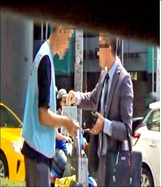 身穿印有協會背心的工讀生,手持「募款箱」於台北捷運站口募款。(記者蔡清華翻攝)