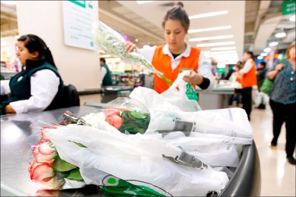 聖地牙哥一家超市的服務人員將玫瑰花裝入塑膠袋。智利3日頒佈塑膠袋禁用法,成為南美洲第一個禁止商業使用塑膠袋的國家。(法新社)