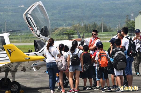 安捷訓練機起降恆春機場引起歡呼,飛行員解說機體。(記者蔡宗憲攝)