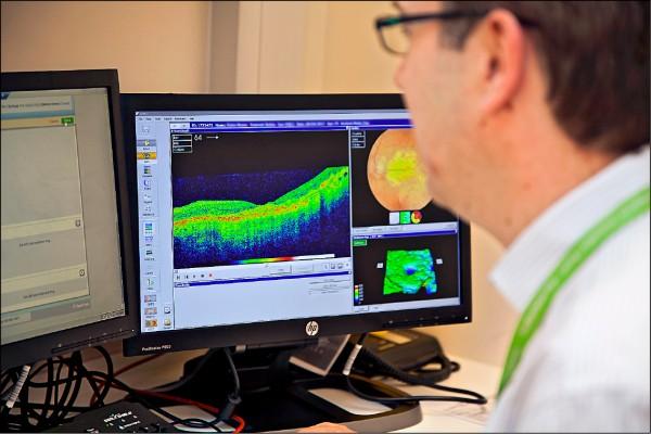 Google母公司Alphabet旗下的人工智慧公司DeepMind,十三日宣告其AI科技診斷眼疾的功力不輸全球頂尖視網膜專家,準確率高達九十四.五%。圖為眼科醫師分析「眼底光學斷層掃描儀(OCT)」成像結果。  (取自網路)