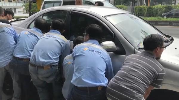 10多名壯漢在轎車兩邊合力抬車。(記者張聰秋翻攝)