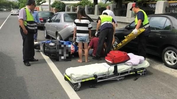 2機車擦撞後,男騎士騎乘的機車,倒在停在路邊的轎車後面,男騎士滑進轎車車盤底下,待救援。(記者張聰秋翻攝)