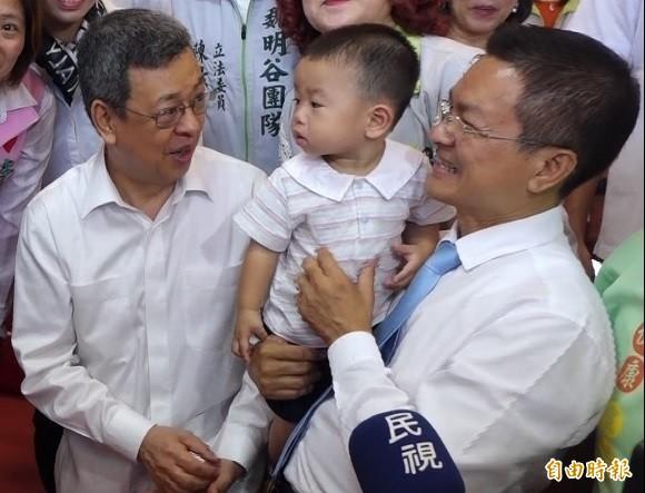 副總統陳建仁(左)到彰化親子館,縣長魏明谷開心抱起(右)幼童。(記者劉曉欣攝)