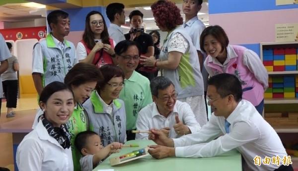副總統陳建仁(圖坐者右二)到彰化親子館,彰化縣長魏明谷(圖坐者右一)等人跟小朋友玩打擊小樂器。(記者劉曉欣攝)