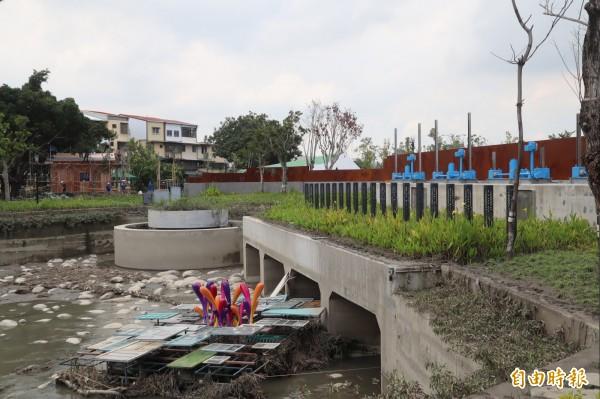 花博豐原園區內的軟埤仔溪滯洪池已乾涸,右側為水閘門,左圓圈處為溢流井。(記者歐素美攝)