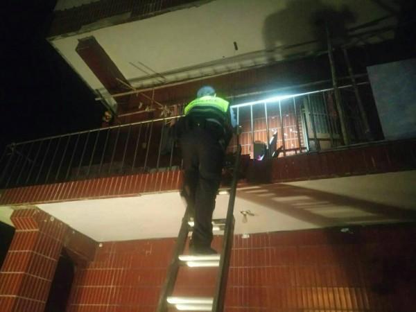 警方借來鋁梯救援爬上2樓陽台。(記者李容萍翻攝)