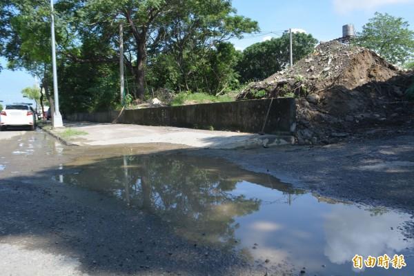 烏日區環河路2段旁「明傳產業園區」堆置的土堆未做好防範措施,近日大雨砂土流出造成側溝堵塞、路面積水。(記者陳建志攝)