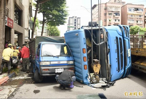 台北市中華路莒光路口23日中午發生翻車意外 ,泥車疑似車速過快,整輛車翻覆在路邊,壓毀停在路邊的汽機車。(記者羅沛德攝)