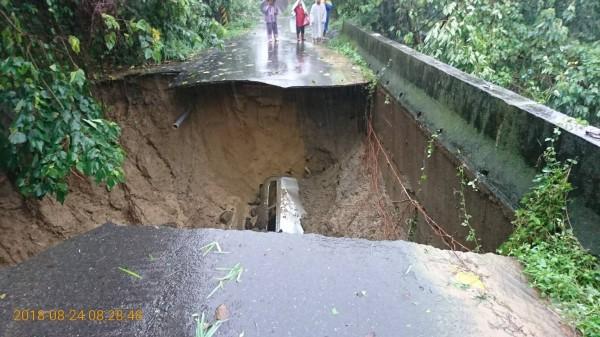 官田區大崎里三層崎產業道路,因大雨沖刷路基,造成路面塌陷破大洞,1輛廂型車摔進坑洞。(記者楊金城翻攝)
