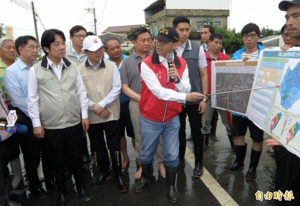 行政院長賴清德(前左一)到台南麻豆埤頭里勘災,聽取台南市水利局簡報。(記者楊金城攝)