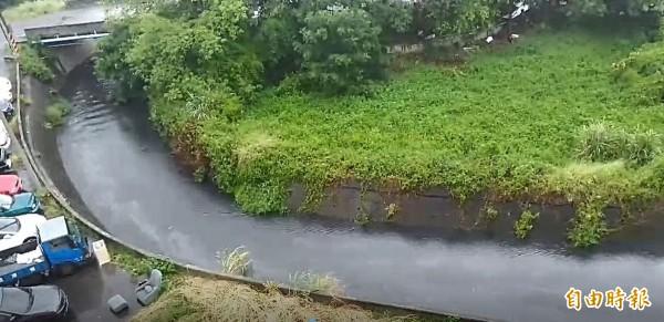 竹南鎮竹興國小後方的射流溝經連日大雨,溪水顏色呈黑褐色,水面上還漂著油汙。(記者鄭名翔攝)