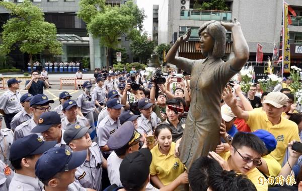 新黨青年軍27日於日本交流協會外舉行「阿嬤站起來,大家站出來」活動,抗議日本干預首座「慰安婦」阿嬤雕像設立於台南。青年軍成員將事先準備好的慰安婦雕像立在日本交流協會對面,要求日本道歉。(記者羅沛德攝)