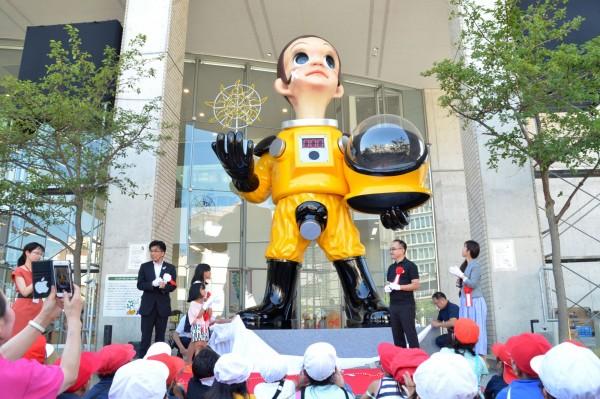 日本福島縣福島市日前在JR福島站附近設置了一個身穿防護服的兒童立像,挨批可能加劇福島核災負面形象。當局今日宣布撤除這座藝術裝置。(法新社)