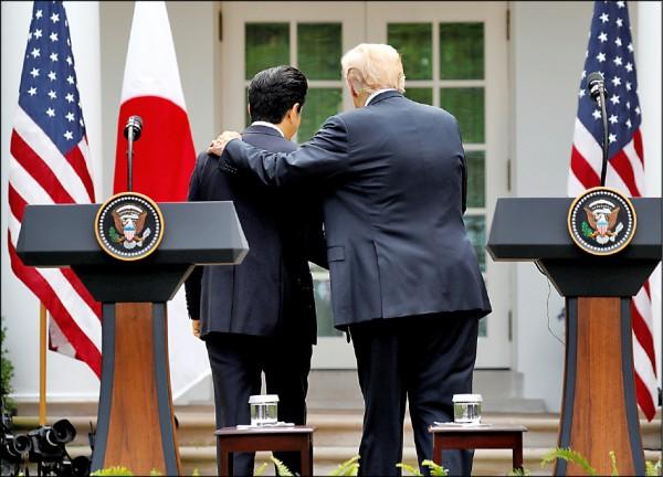 美國總統川普(右)六月間在白宮與來訪的日本首相安倍晉三會談後召開聯合記者會,結束後搭著安倍的肩膀離開。據稱川普當時與安倍論及美日貿易時,曾脫口說出「我記得珍珠港」。(路透檔案照)