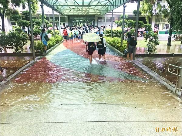 開學日大雨來考驗!午後雷雨造成淹水,內壢國中中庭一片汪洋,家長紛紛進入校園接孩子,再一起涉水回家。(記者李容萍攝)