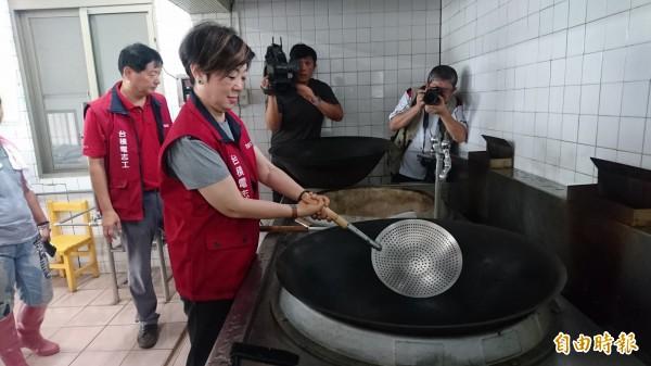 張淑芬參觀學校廚房,試拿鍋瓢。(記者楊金城攝)