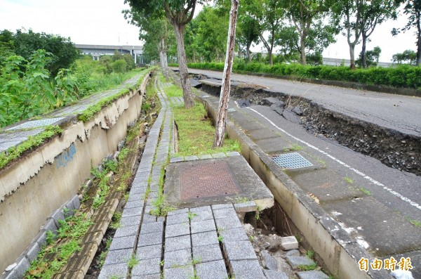 不堪豪雨侵襲,台南高鐵站特定區歸仁二路嚴重塌陷。(記者吳俊鋒攝)