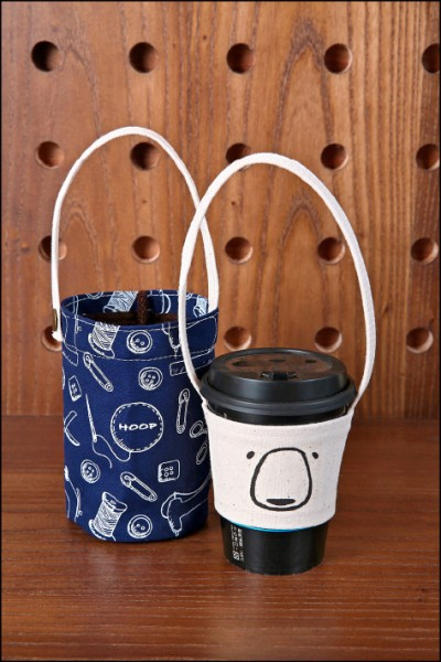 收納式水壺袋/1個255元(左,直徑10cm×20cm)、帆布手提杯套/150元(右,直徑13cm×6.5cm) 收納式水壺袋可折疊收納成一小捲,方便攜帶,有多樣顏色可選;帆布手提杯套則設計有簡單風格的插畫。(記者潘自強/攝影)