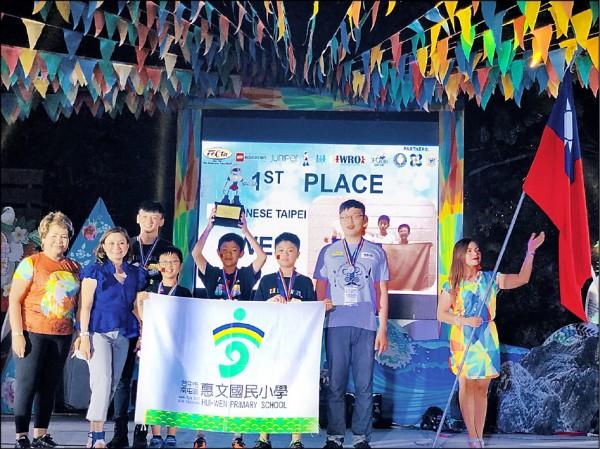 惠文國小參加國際奧林匹克機器人大賽友誼邀請賽奪冠,拿自備的國旗上台領獎。(圖:惠文國小提供)