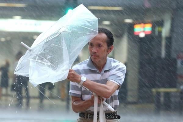 燕子颱風挾帶暴雨,強大的風力讓當地民眾雨傘毀損。(歐新社)