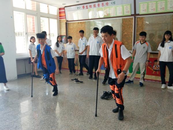 暨中學生腳綁重量臂帶拿枴杖走路,體驗老人家老化的痛苦。(暨大附中提供)