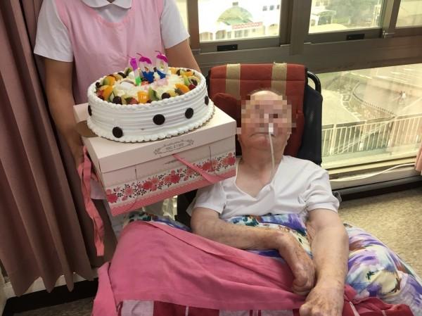 張老奶奶因腦中風後呈植物人狀態,入住創世基金會苗栗分院,今年滿100歲,院方準備了插著百歲蠟燭的蛋糕替她慶生。(圖由創世基金會苗栗分院提供)