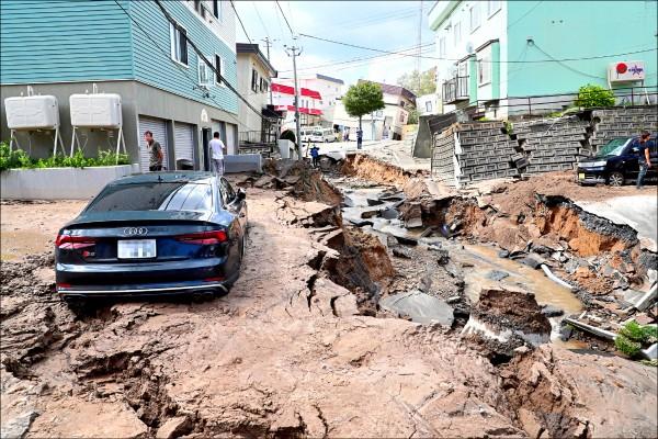 札幌市內街道在強震後出現土壤液化現象,造成附近民宅和汽車陷落,馬路裂開。(歐新社)